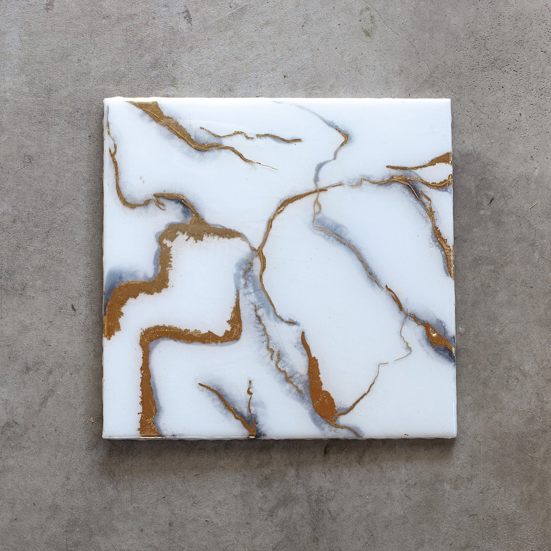 Kintsugi is an original resin and pigment painting by Siroh and Ivy on wood canvas with white and grey in a marble patter with gold leaf accents