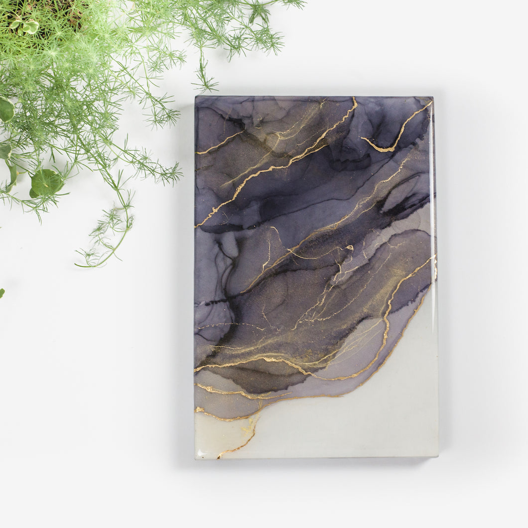 Ink well is a rectangular fine art resin painting by Siroh & Ivy with overlapping layers of grey alcohol ink overlaid with gold leafing and shimmering glitter
