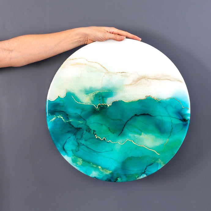 Siroh & Ivy original piece of resin art on circular canvas with hues of green alcohol ink and gold leafing
