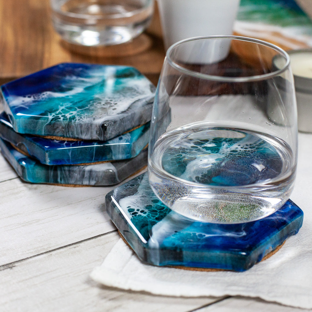 Hexagon marble coasters with an ocean design painted with food-safe resin on a white wood table with glasses of wine