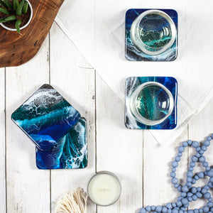 Square marble coasters with an ocean design painted with food-safe resin on a white wood table with glasses of wine