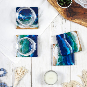 Square wood coasters hand painted with a striking blue ocean design sitting on top of a white wood table top