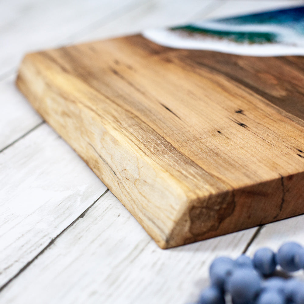 Handcrafted maple wood serving board with an ocean inspired resin design sitting on a white wood table with glasses of wine