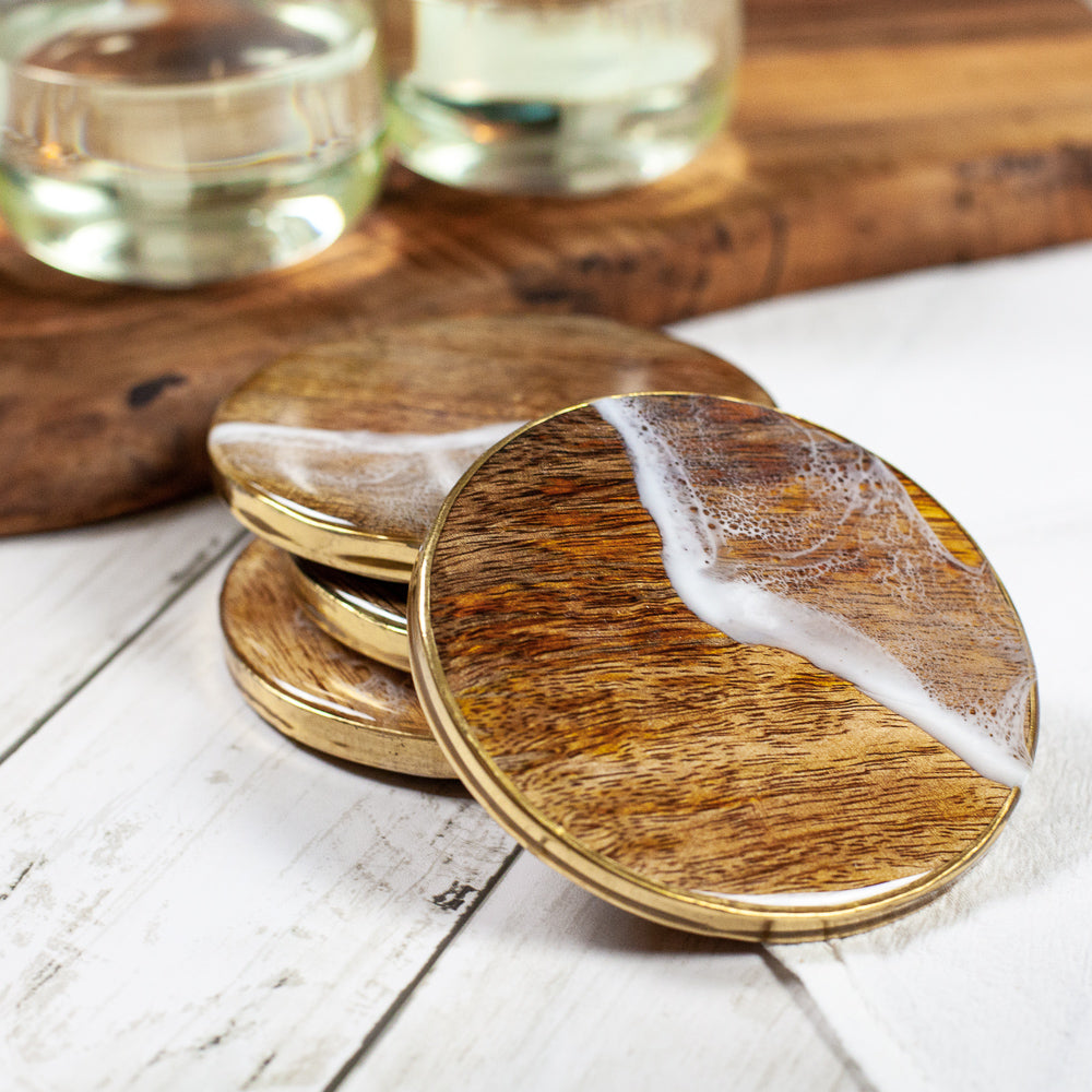 Natural wood coasters with gold metal sides and custom sea foam resin painted design on a white wood table with glasses of wine