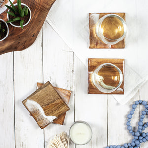 Natural wood coasters with sea foam resin painted design on a white wood table with glasses of wine
