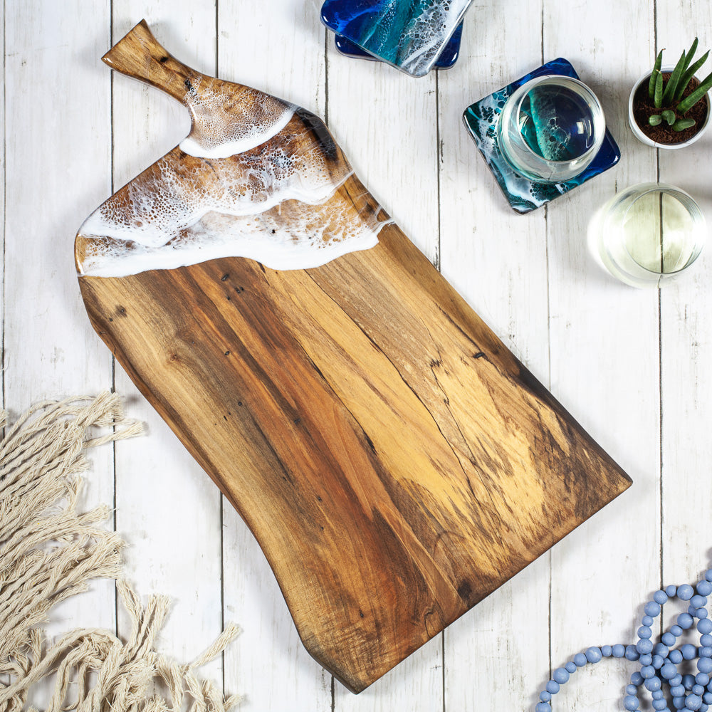 Handcrafted maple wood serving board with a sea foam inspired resin design sitting on a white wood table with glasses of wine