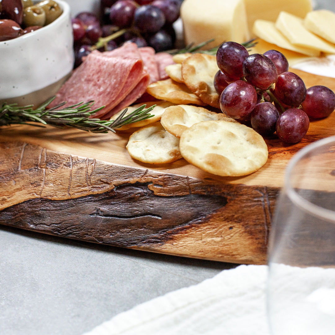 Solid cherry serving board with sea foam design in resin and a meat and cheese charcuterie spread