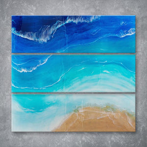 Aerial is a Siroh & Ivy original piece of resin art spanning 3 rectangular canvases but with one continuous design that mimics an overhead view of a beach and the ocean, blue water, white waves, and gold sand