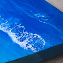 Load image into Gallery viewer, Aerial is a Siroh & Ivy original piece of resin art spanning 3 rectangular canvases but with one continuous design that mimics an overhead view of a beach and the ocean, blue water, white waves, and gold sand