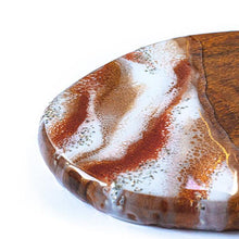 Load image into Gallery viewer, Glitter Bomb is a small wood cheeseboard hand painted by Siroh & Ivy that uses layers of resin alternating in colors of red, gold, and white with heavy silver glitter accents