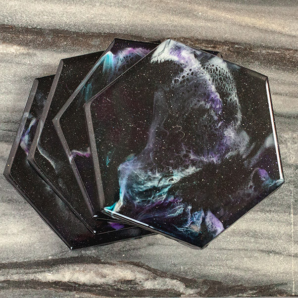 Galaxy themed hand-painted coasters from Siroh & Ivy with blue, white, pink, and purple colors that resemble a nebula with a shimmering star effect throughout