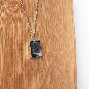 Hand-painted necklace from Siroh & Ivy featuring a rectangular pendant filled with black and white pigments and glitter that resembles a galaxy and a silver colored adjustable chain