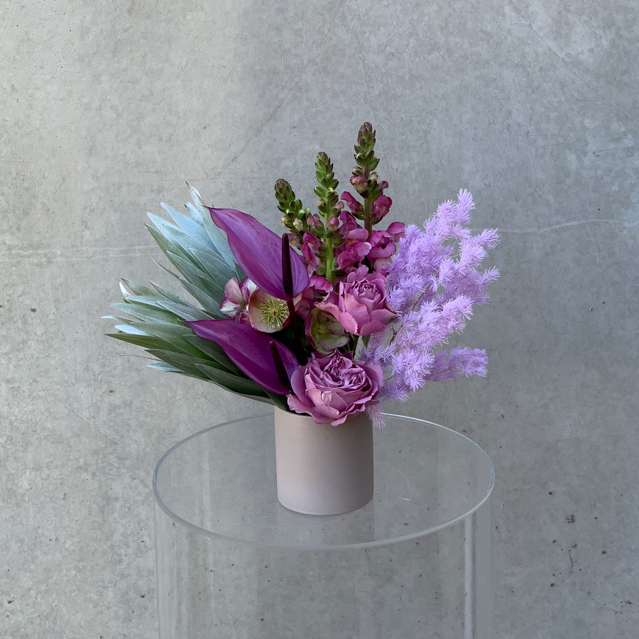 Small vase arrangement featuring assorted mauve flowers