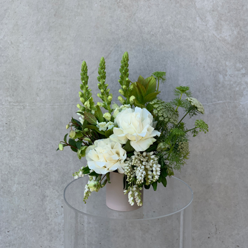 Small vase arrangement featuring assorted white & green toned flowers