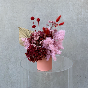 A pink & red toned preserved flower arrangement in a coral pink vase.