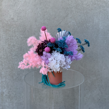 Preserved flower arrangement of mixed bright pastel colours displayed in a coral pink vase.