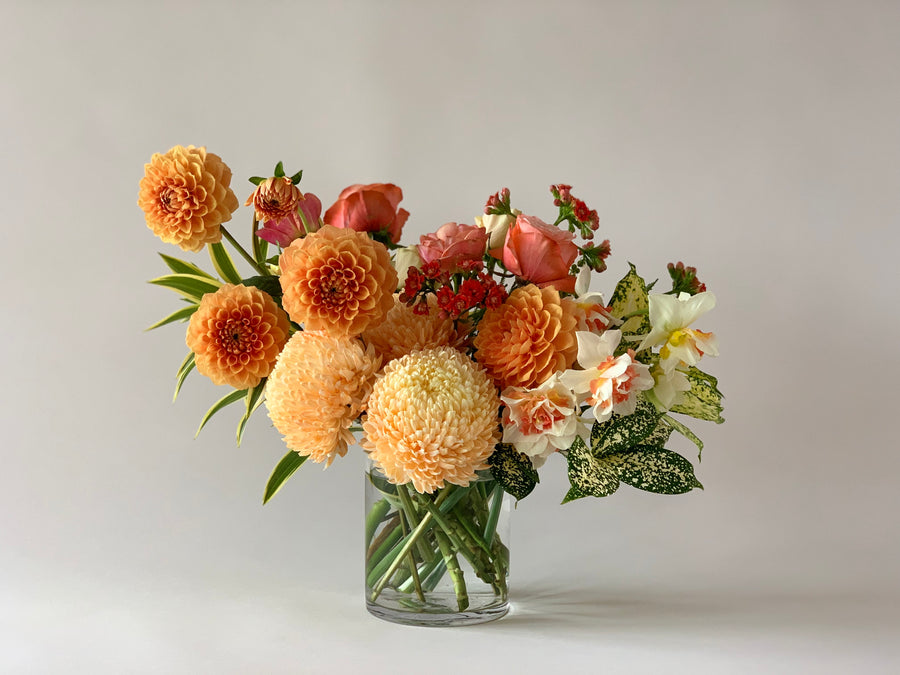 Bouquet of orange toned flowers in vase