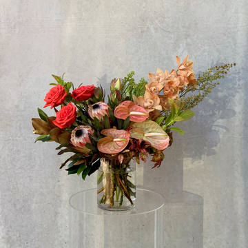 A vibrant arrangement of bronze & red toned flowers & foliage