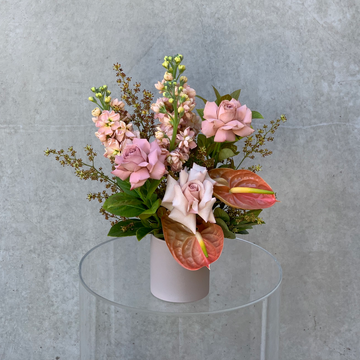 Small vase arrangement featuring assorted taupe & nude toned flowers