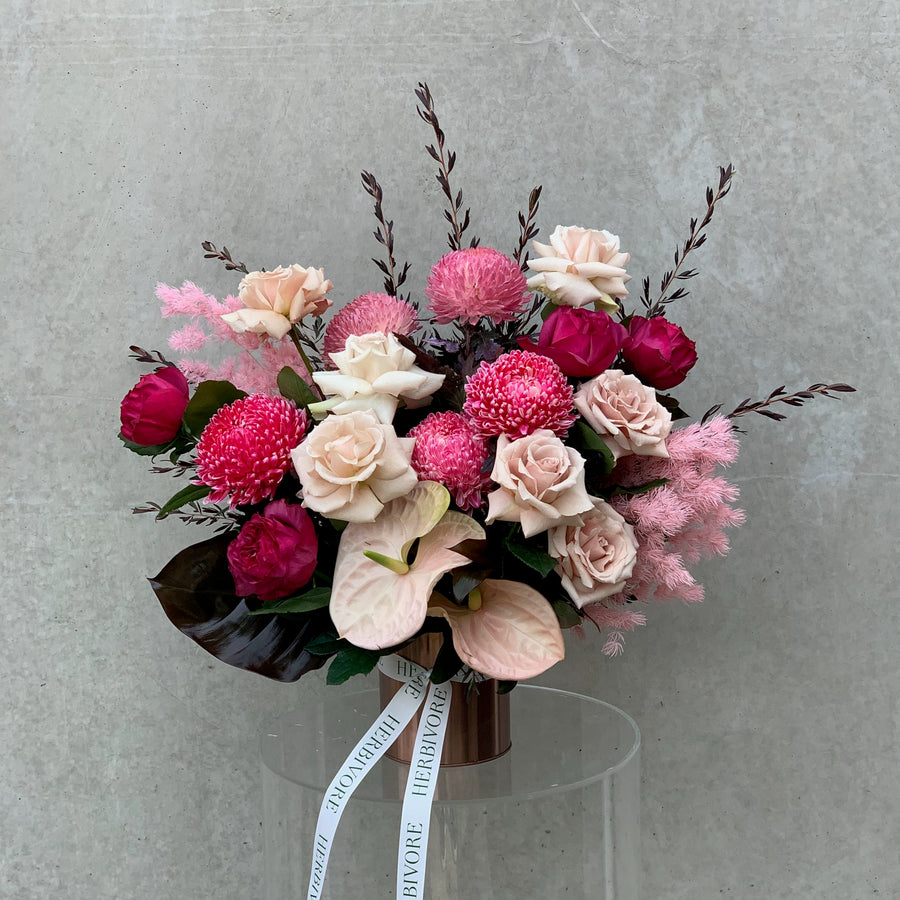 Pink flower arrangement in rose gold vase