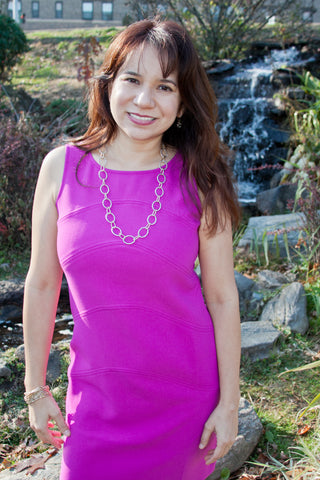 Nicole Benedicto Elden wearing a hot pink dress, standing in front of a waterfall and some flowers.
