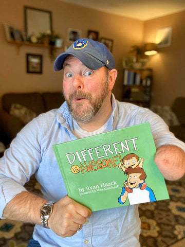 """Ryan Haack, holding up the book """"Different is Awesome"""". He has one arm, is wearing a hat and a blue shirt, and has a silly smile on his face."""