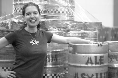 Hathaway Terri-Pogue from Ale Asylum posing in front of a beer barrel with the Ale Asylum logo. Image is in gray tones. Hathaway is smiling with her hair in a pony tail and is wearing an ale asylum t-shirt.