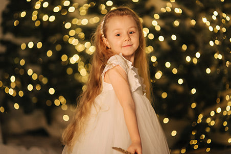 Portrait of little girl in front of the Christmas tree