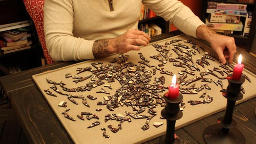 Whitney's partner Justin, a certified adult man, working on a puzzle by candlelight