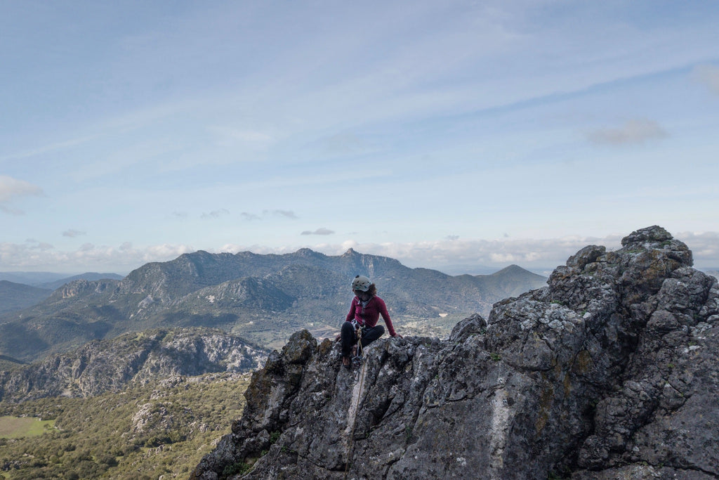 Rock climber at top of crag in Sierra de Grazalema, Spain