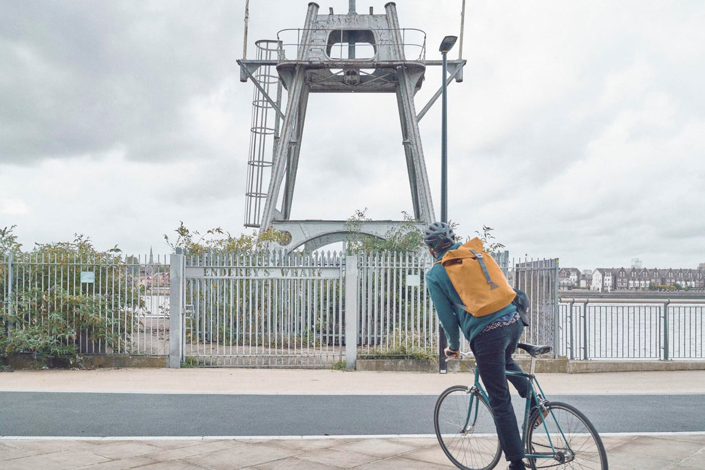 Photographer Joe McGorty cycling the Thames Footpath wearing an orange waterproof Utility Archive backpack