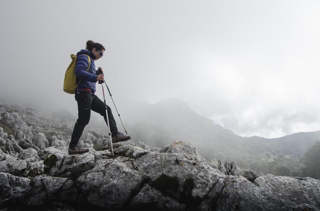 Hiker striding over boulders on cloudy mountainside.
