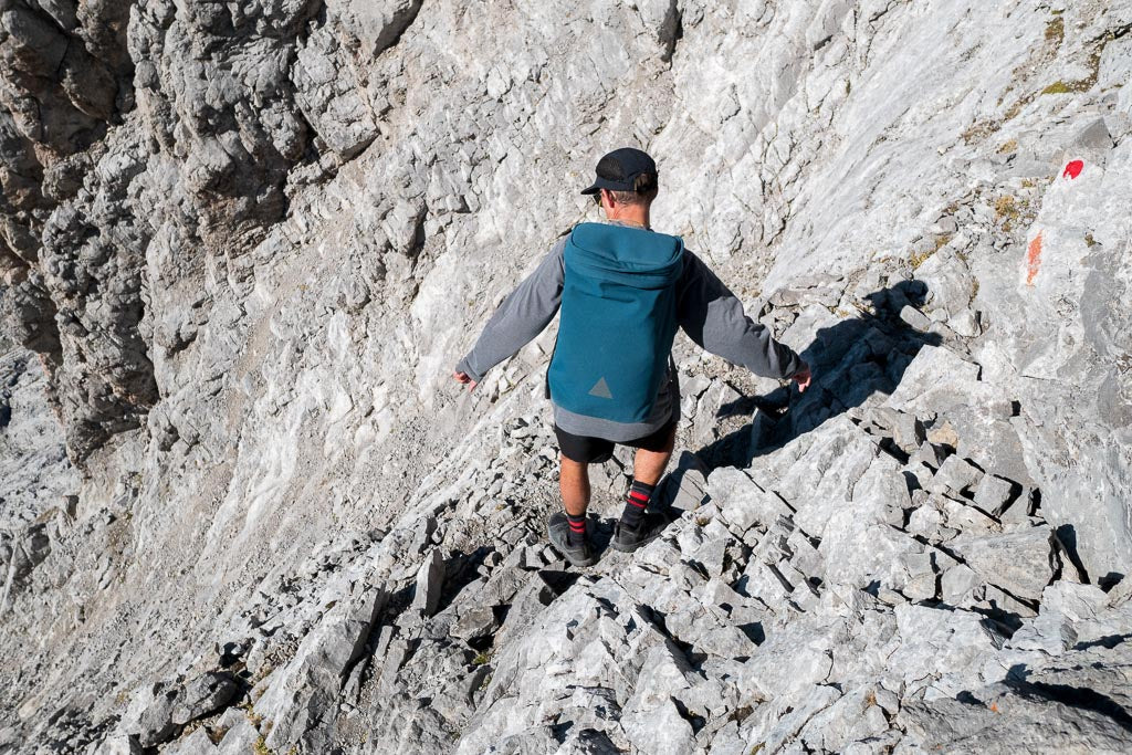 Man with blue backpack hiking down steep rocky path