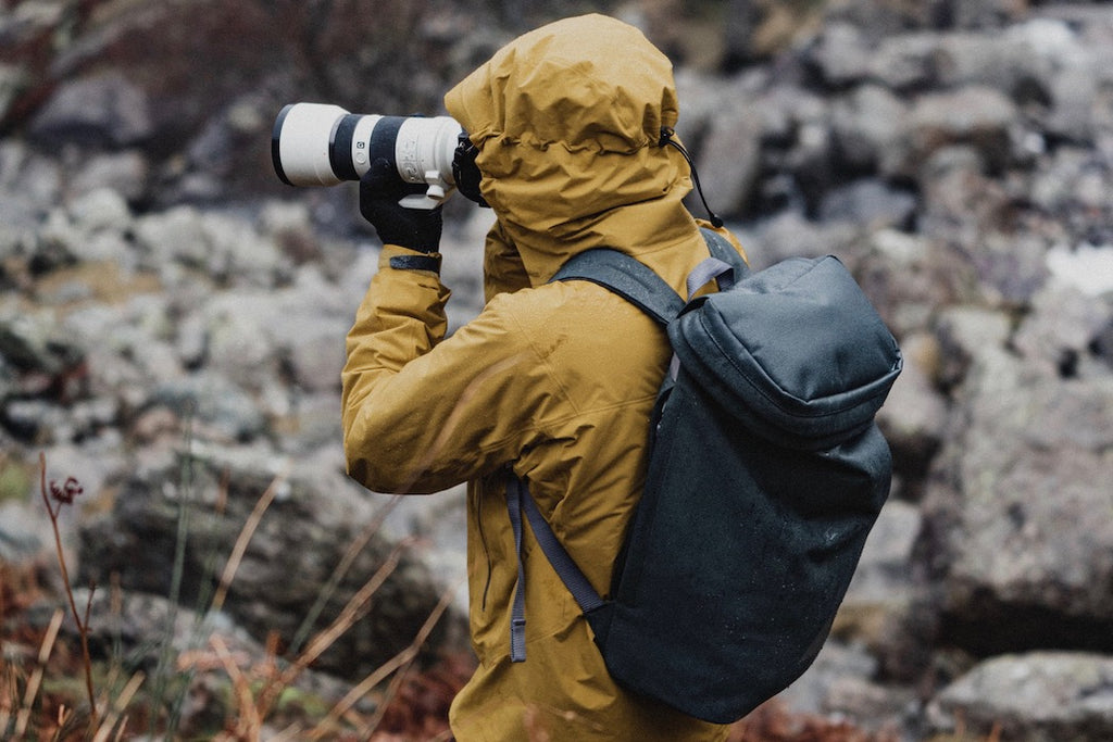 Photographer outdoors on wet day in yellow rain jacket and grey backpack