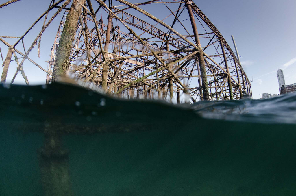 Partially underwater photograph of derelict Brighton West Pier, blue skies