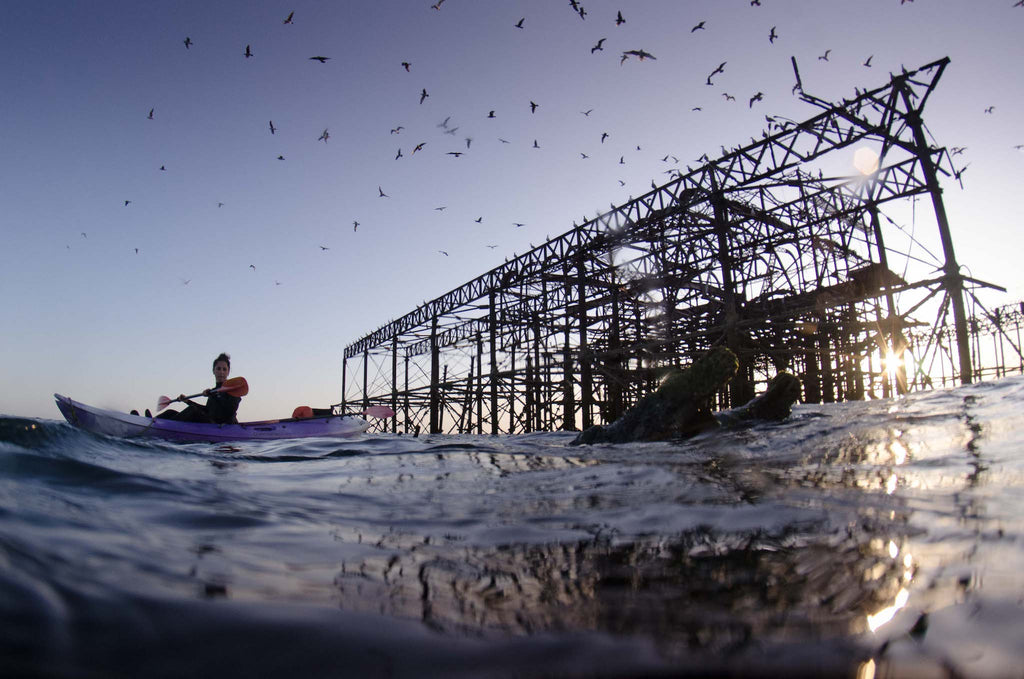 Derelict Brighton West Pier as sun sets on clear day, kayak and seagulls