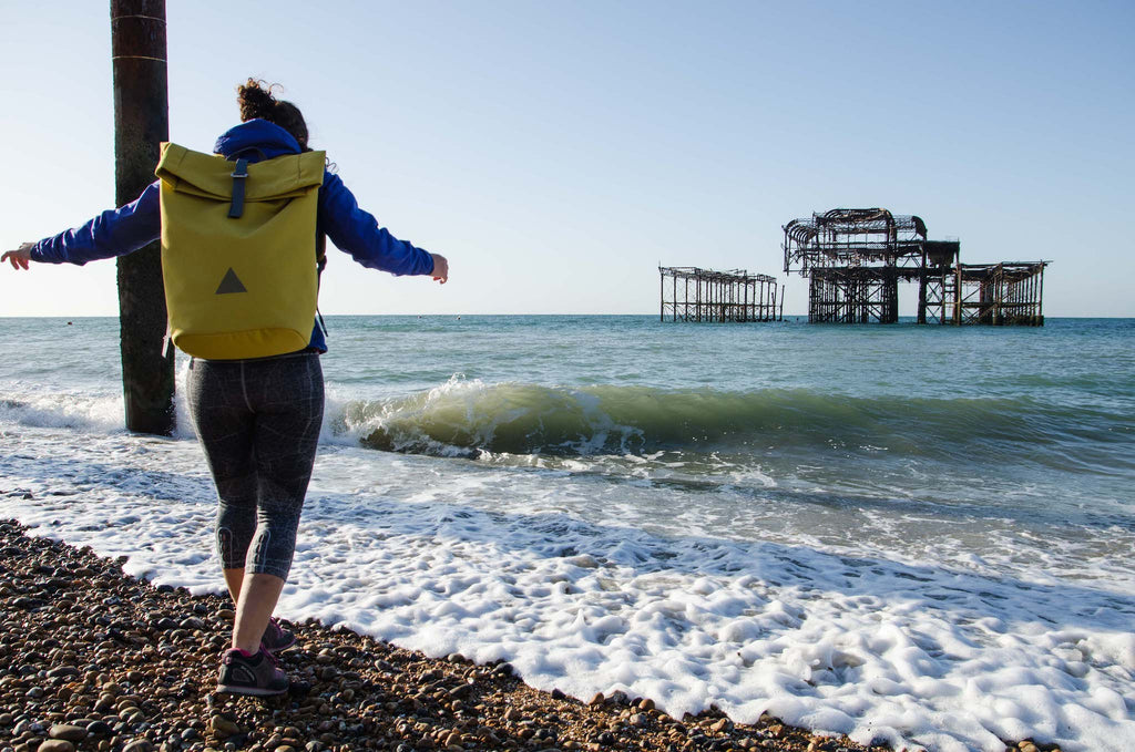 Woman with yellow backpack, skipping in waves, Brighton beach, West Pier in background
