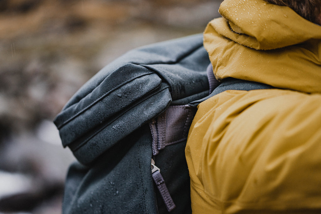 Hiker on a wet day in yellow rain jacket carrying grey backpack