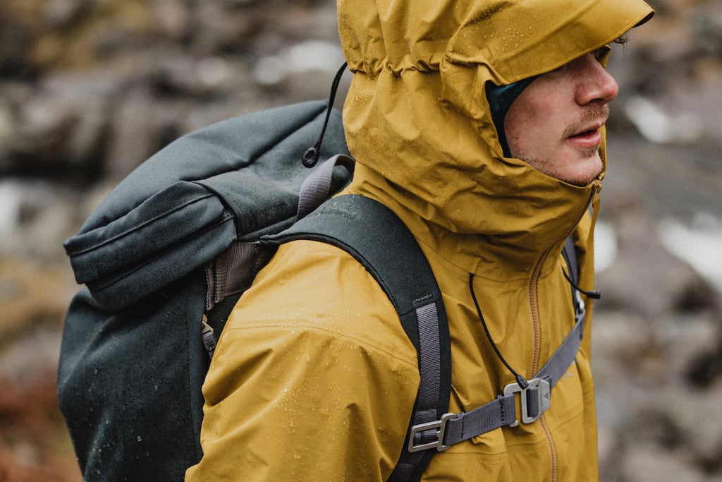 Man walking on a soaking wet day with yellow jacket and grey backpack