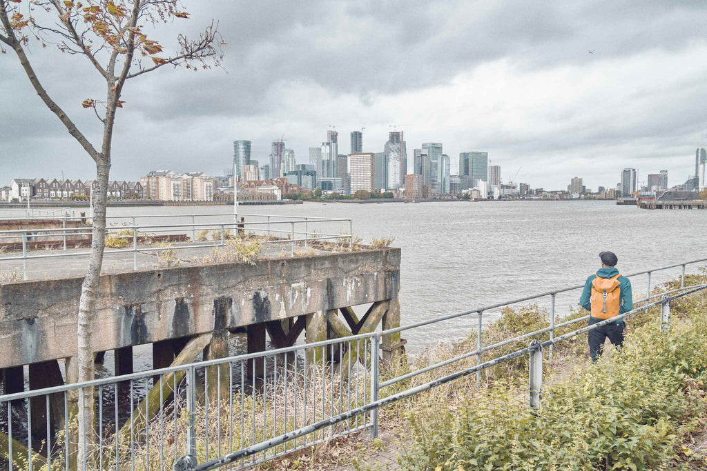 Photographer Joe McGorty wears an orange waterproof backpack looking across the Thames to the London Docklands skyline