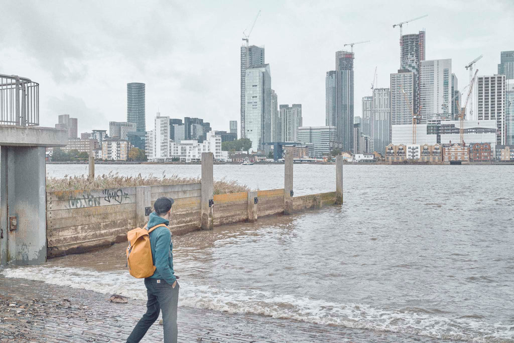 Photographer Joe McGorty wearing an Utility Archive backpack looking across the Thames to the London Docklands skyline