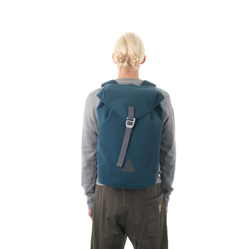 Woman carrying blue waterproof flap backpack.