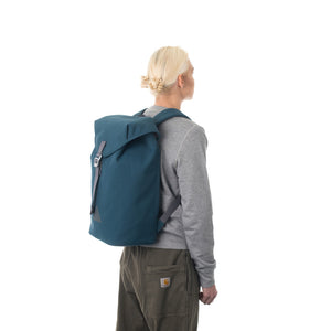 Woman carrying blue flap backpack.