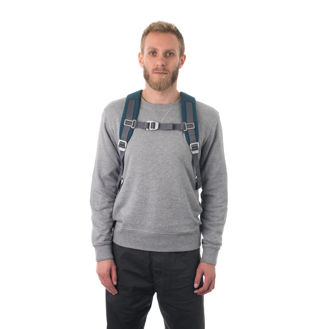 Man carrying blue flap backpack with padded shoulder straps.