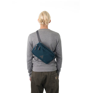 Woman wearing blue bumbag across across back.