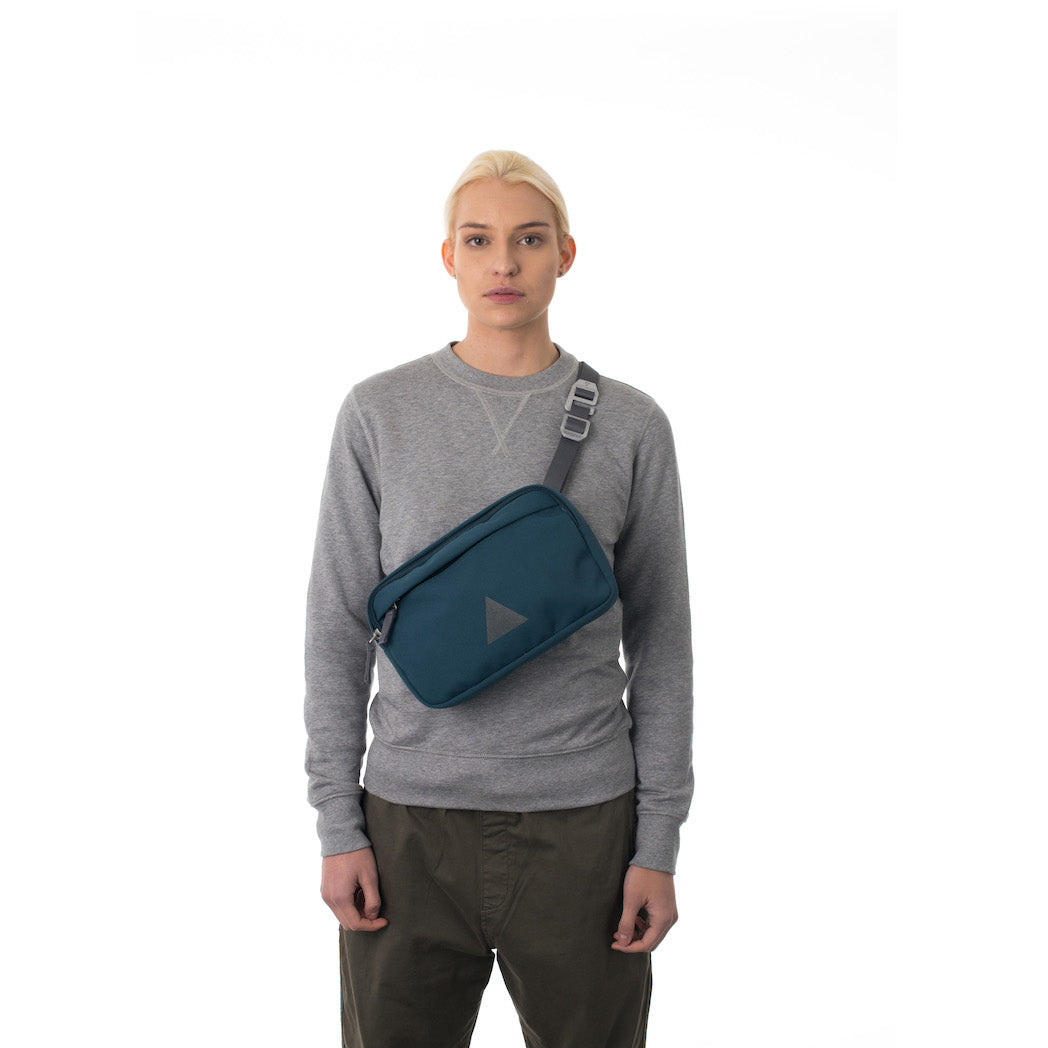 Woman wearing blue cross body bag.