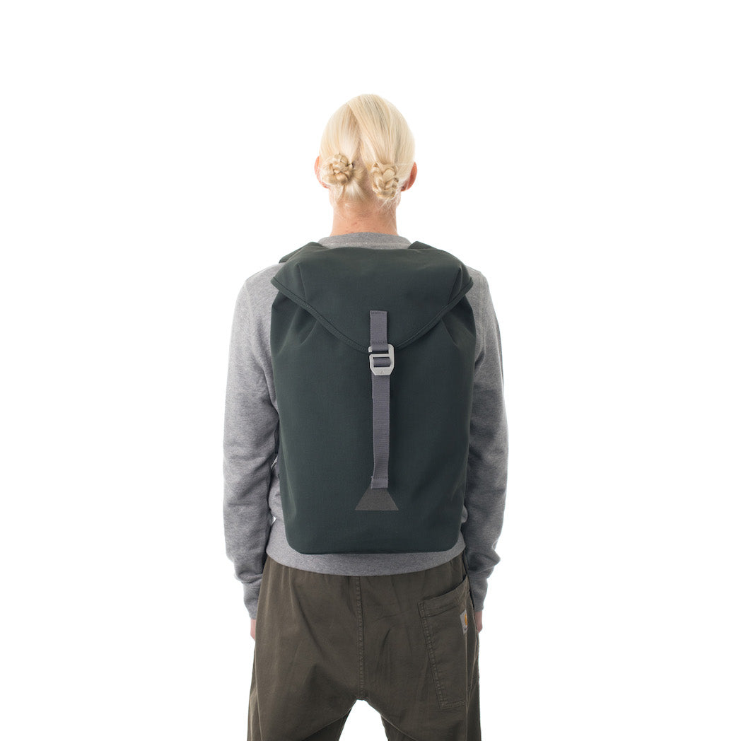 Woman carrying grey waterproof flap backpack.