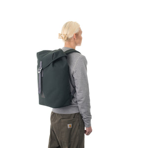 Woman carrying grey flap backpack.