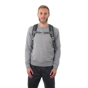 Man carrying grey flap backpack with padded shoulder straps.