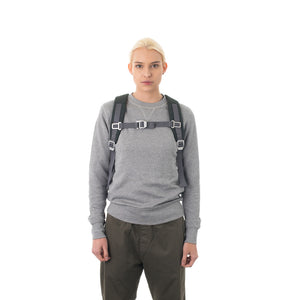 Woman carrying grey backpack with padded shoulder straps.